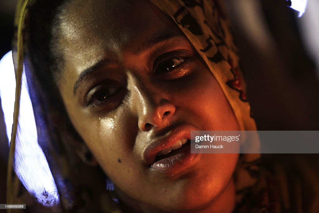 A woman of the Sikh Temple of Wisconsin mourns while attending a candle light vigil held at the Oak Creek Community Center on the National Night Out event August, 7, 2012 Oak Creek, Wisconsin. A suspected gunman, 40-year-old Wade Michael Page, allegedly killed six people at the temple August 5, was shot to death by police at the scene. He was an army veteran and reportedly a former leader of a white supremacist heavy metal band. Three others were critically wounded in the attack.
