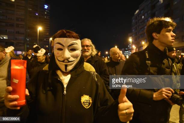 A woman of the Trade Union of taxi drivers Elite with a mask of anonymity during the protest of taxi drivers in Barcelona against Uber and Cabify...