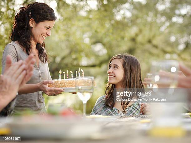 Woman offering birthday cake to girl