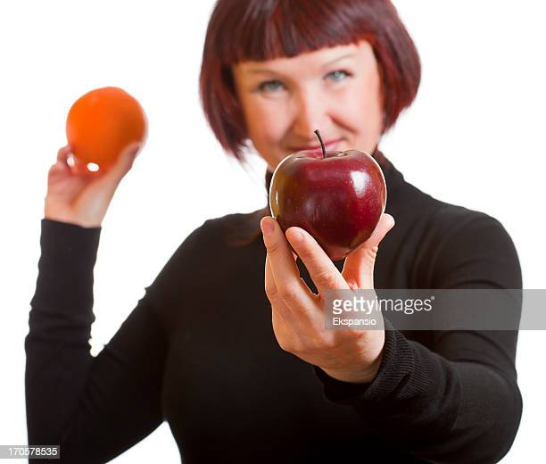 Woman Offering Choice of Red Apple or Orange