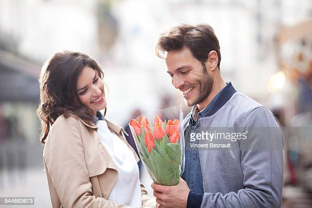 Woman offering flowers to a man in the street
