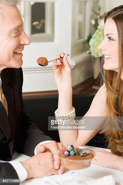 woman offering man spoonful of chocolate cream in restaurant - chocolate mousse stock pictures, royalty-free photos & images