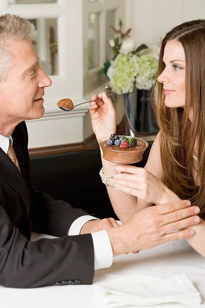 Woman offering man spoonful of chocolate cream in restaurant