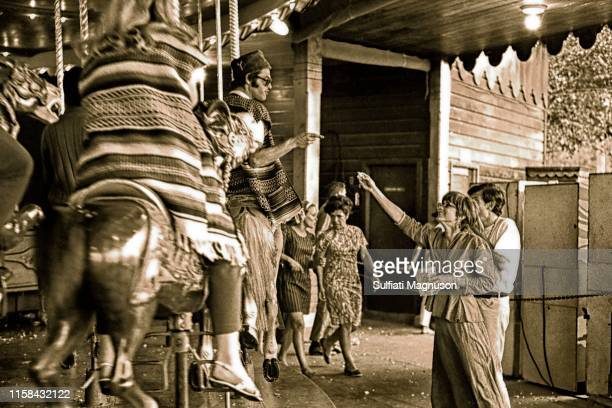 Woman offering popcorn to a man riding the carousel, dressed in a serape and a hat, who is pointing at her at the 1st Elysian Park Love-In on March...