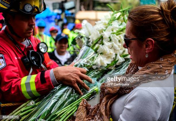 A woman offers a bunch of flowers to a firefighter near the site where rescuers keep on digging for survivors still buried under the rubble from a...