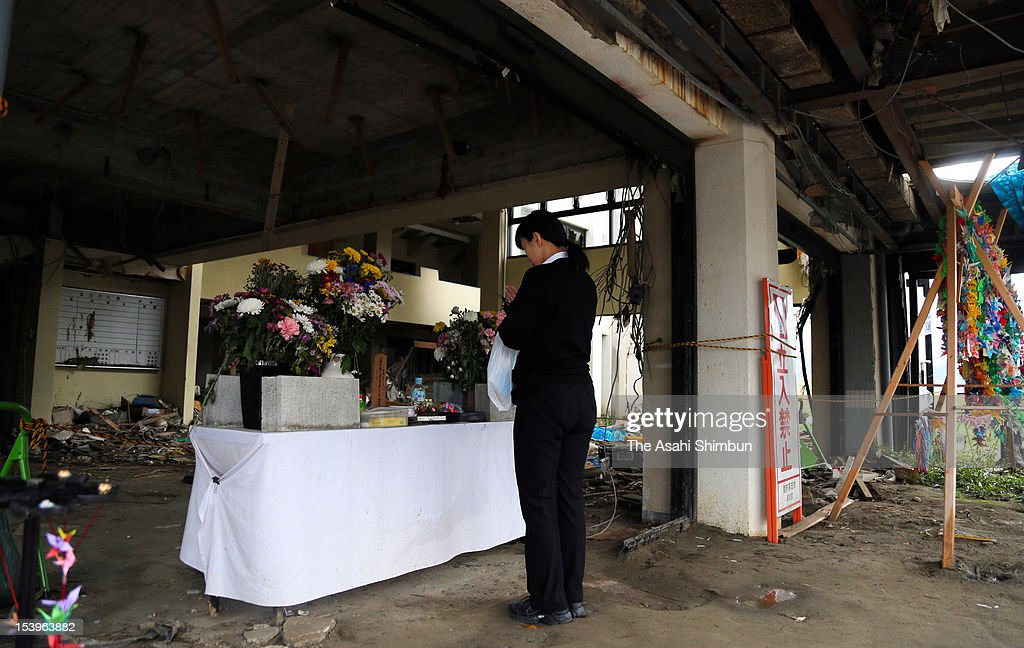 A woman offers a flower bunch to an alter arranged at the damaged Rikuzentakata Shimin Kaikan Hall on October 11, 2012 in Rikuzentakata, Iwate, Japan. Rikuzentakata City will clear all the destroyed public buildings by March 2013. Japan marks 19 months anniversary of the earthquake and following tsunami, which caused more than 20,000 casualties.