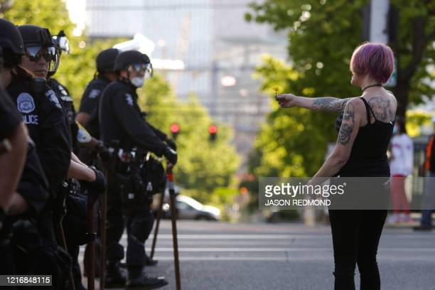 Woman offers a flower to Seattle police officers as people protest the death of George Floyd in the Capitol Hill neighborhood of Seattle, Washington...