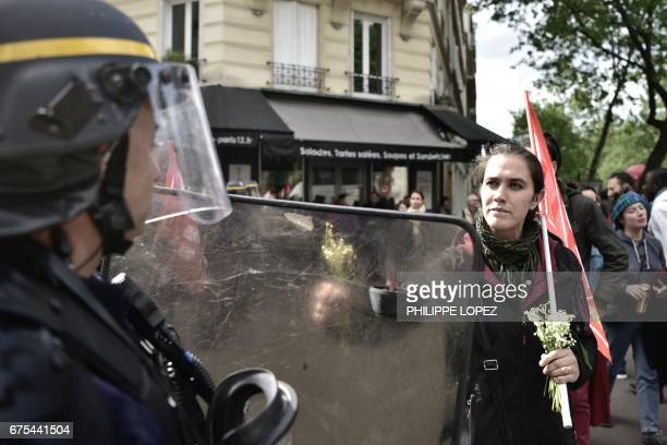 A woman offers a some lilies of the valley to a French antiriot policeman during a march for the annual May Day workers' rally in Paris on May 1 2017...