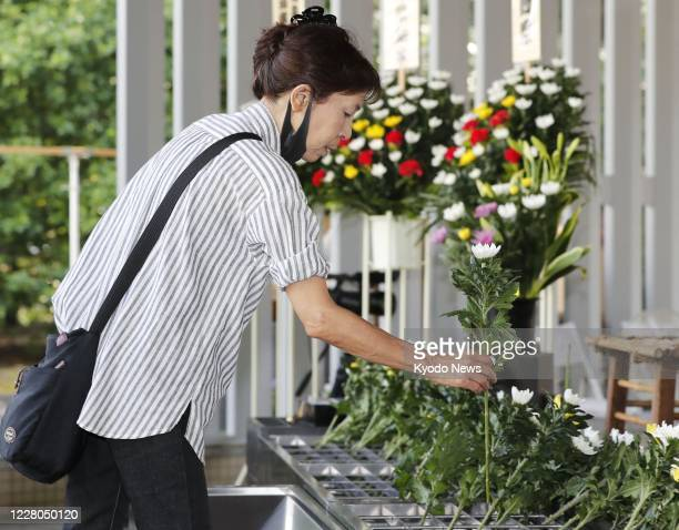 Woman offers flowers at the Chidorigafuchi National Cemetery in Tokyo for unidentified war dead on Aug. 15 as Japan marks 75 years since its...