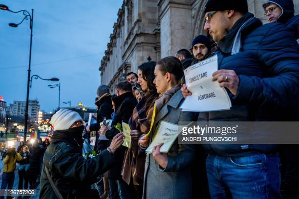Woman offers flowers to magistrates that protest in front of the Court of Appeal, on February 22 in Bucharest, Romania. - Hundreds of judges...