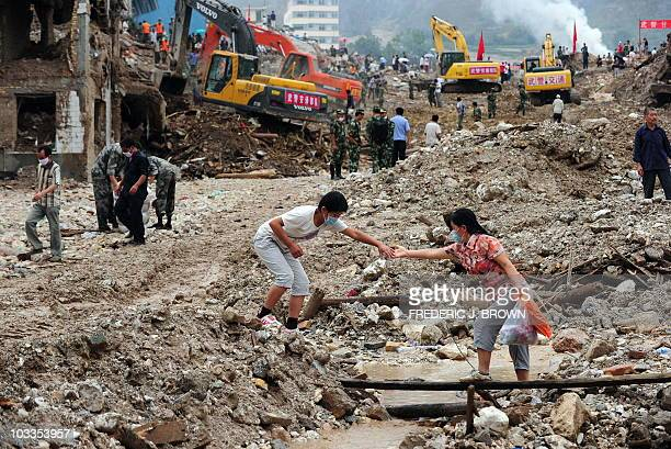 Woman offers her hand to help another cross rubble and dedris as rescuers with excavators works in the aftermath of a landslide in Zhouqu on August...