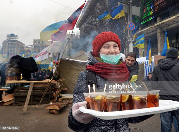 A woman offers hot tea at a barricades set by Ukrainian ProEuropean opposition activists at Kiev's Independence Square on December 17 2013 Ukraine's...