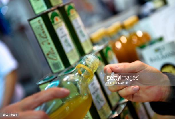 A woman offers olive oil to taste during the Paris international agricultural fair at the Porte de Versailles exhibition center in Paris on February...