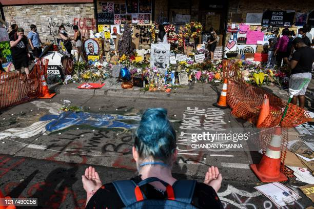 A woman offers prayers as she pays her respects at a makeshift memorial in honour of George Floyd on June 3 2020 in Minneapolis Minnesota Former...