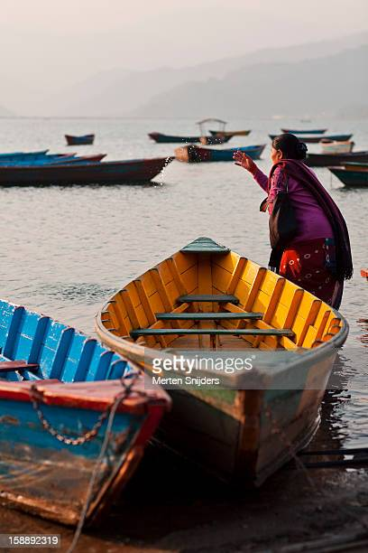 woman offers prayings at phewa lake - merten snijders stock pictures, royalty-free photos & images