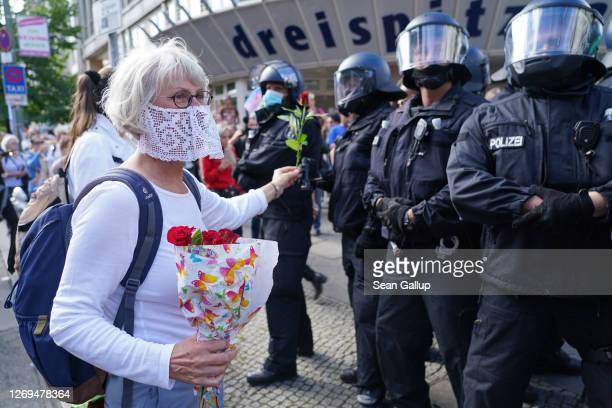 A woman offers riot police flowers while marching with coronavirus skeptics rightwing extremists and others in protest against coronavirusrelated...