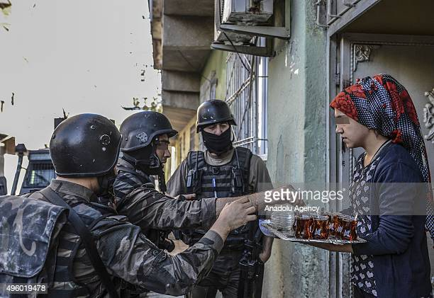 A woman offers tea to members of Turkish security forces as they carry out an operation against PKK terrorist organization in the Sur district of...