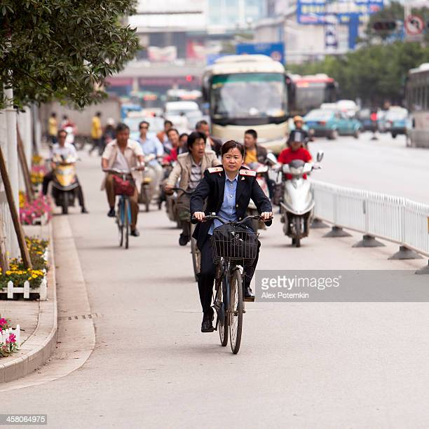woman - officer on the bicycle - kunming stock photos and pictures