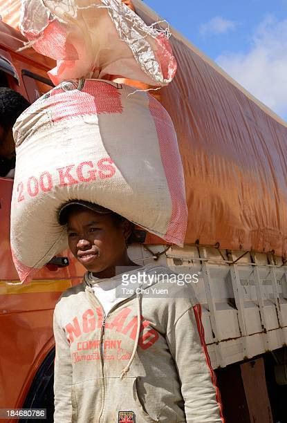 Woman offloading heavy bags from a truck in Manjakandriana, Madagascar and carrying it on her head.