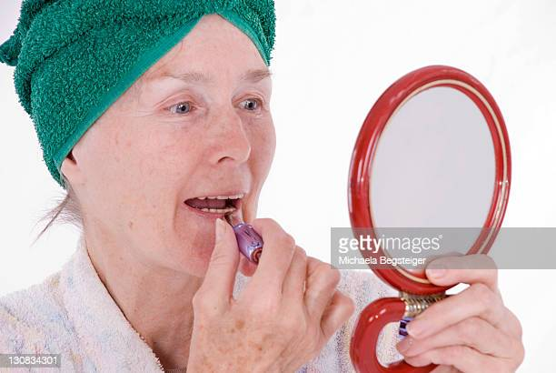 woman, older than 65 years, putting on makeup - 65 69 years stock pictures, royalty-free photos & images