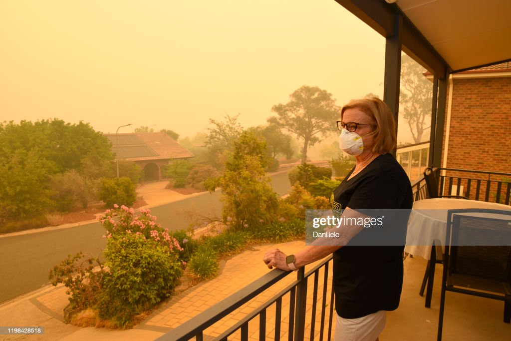 A woman, on a balcony, wears a face mask to protect herself against very dangerous level of air pollution.  A thick yellow fog coming from the nearby forest fires covers Canberra city. : Stock Photo