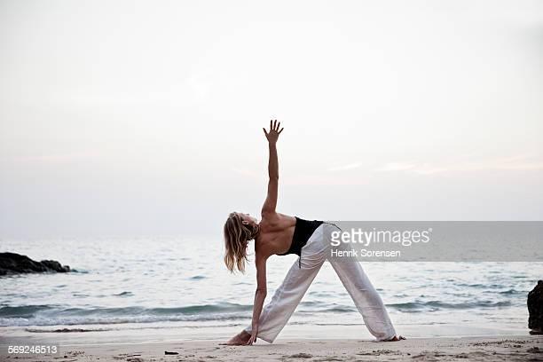 Woman on a beach doing yoga