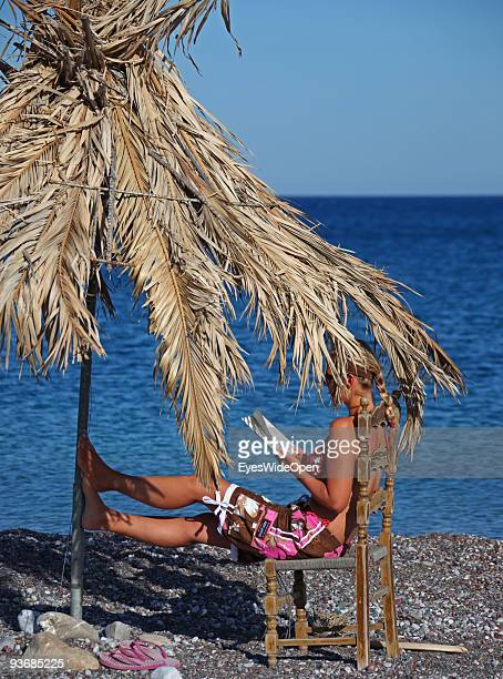 A woman on a beach reading a book near Lindos on July 16 2009 in Rhodes Greece Rhodes is the largest of the Greek Dodecanes Islands