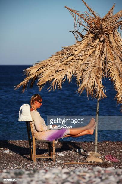 A woman on a beach working with a notebook near Lindos on July 16 2009 in Rhodes Greece Rhodes is the largest of the Greek Dodecanes Islands