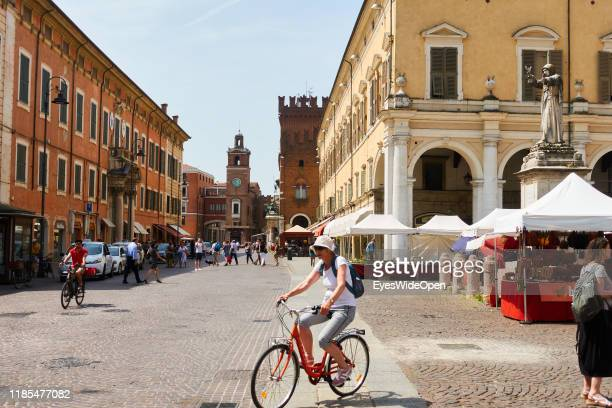 Woman on a bicycle and tourists in the historic center at Piazza Cattedrale on June 8, 2019 in Ferrara, Italy.