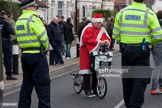A woman on a bicycle dressed in a Father Christmas suit waiting to cross a line of police officers in a closedoff street outside Fratton Park stadium...