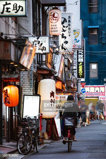 woman on a bicycle in a small alley, shinjuku, tokyo - tokyo japan stock pictures, royalty-free photos & images
