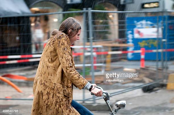 woman on a bicycle in pouring rain - suede stock pictures, royalty-free photos & images