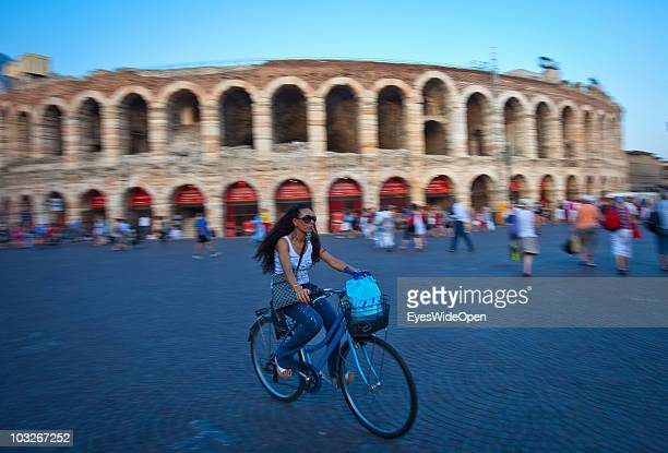 Woman on a bicycle is riding in front of the Arena of Verona on July 14 2010 in Verona Italy The famous Arena di Verona is popular for the annual...