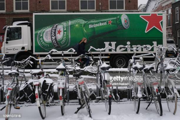 A woman on a bicycle passes a truck of Heineken beer during a snow fall on January 22 in Leiden Netherlands