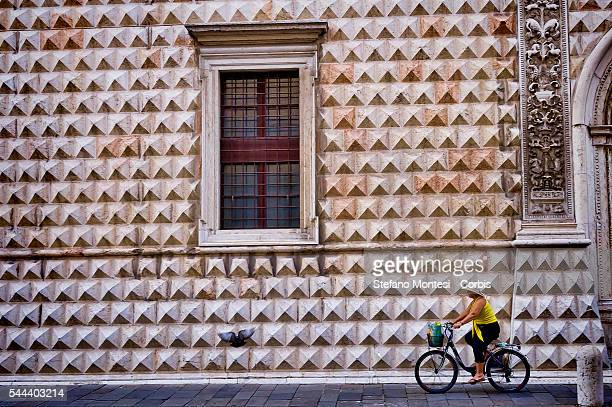 Woman on a bicycle passes in front facade of Diamanti palace architect Biagio Rossetti historic centre of Ferrara on June 30 2016 in Ferrara...