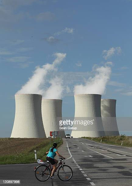 A woman on a bicycle rides by the four cooling towers of the Temelin nuclear power plant on August 11 2011 near Temelin Czech Republic CEZ the Czech...
