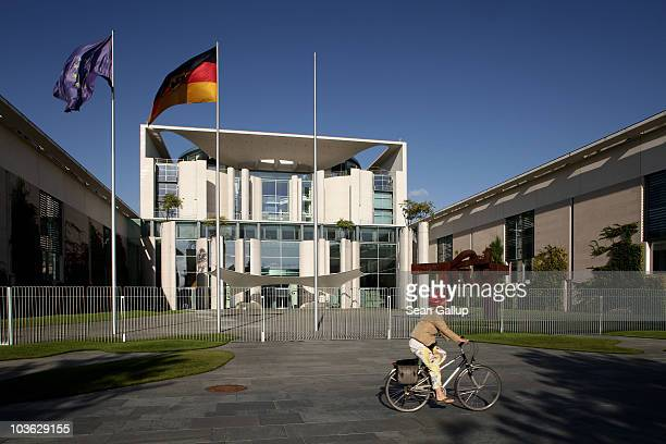 A woman on a bicycle rides past the Chancellery on August 25 2010 in Berlin Germany The Chancellery houses the offices of German Chancellor Angela...