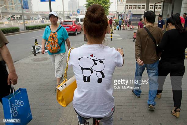 A woman on a bicycle wearing a tshirt with a motif of two panda bears kissing cycling past the Zhongguancun eplaza Beijing China