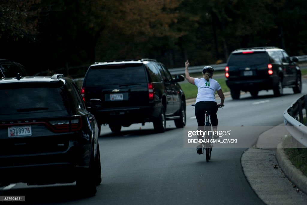 A bicyclist flips off the Trump motorcade, Sterling, Virginia, October, 28, 2017.