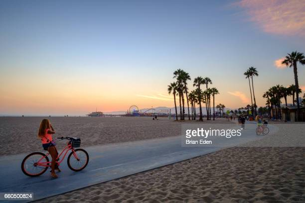 a woman on a bike stops to take a photo of the sunset on her cell phone at sunset on santa monica beach - santa monica stock-fotos und bilder