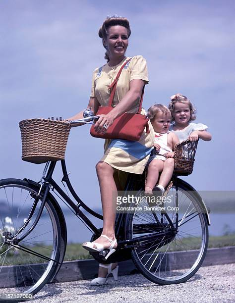 A woman on a bike with two children in the basket seat New York State 1946
