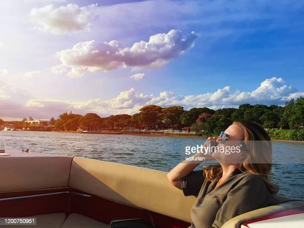 kvinna på en båt som håller en mobiltelefon, - brasilia bildbanksfoton och bilder
