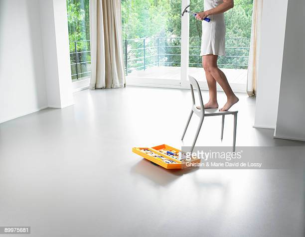 Woman on a chair, toolbox on the floor
