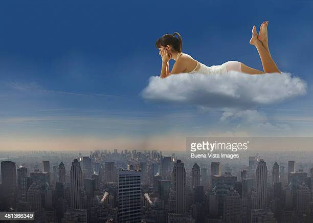 Woman on a cloud watching a city below
