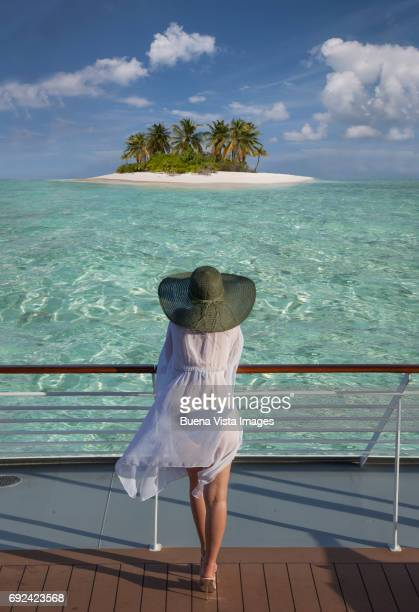 woman on a cruise ship watching a solitary island - kreuzfahrtschiff stock-fotos und bilder