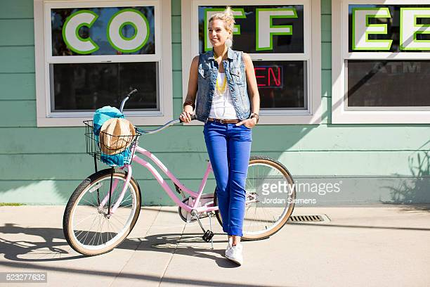 Woman on a cruiser bike standing in front of a coffee shop, Santa Cruz, California, USA
