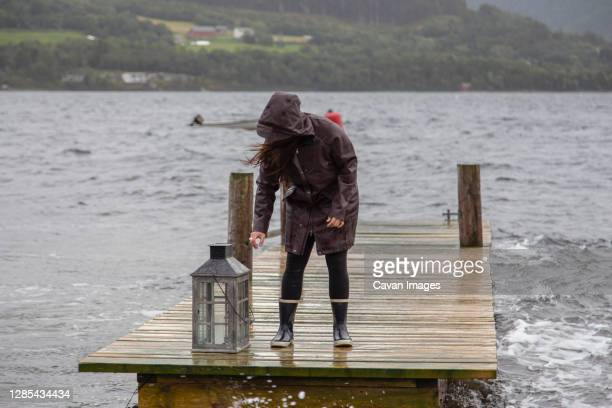 a woman on a dock bends to pick up a lantern - vildmark bildbanksfoton och bilder