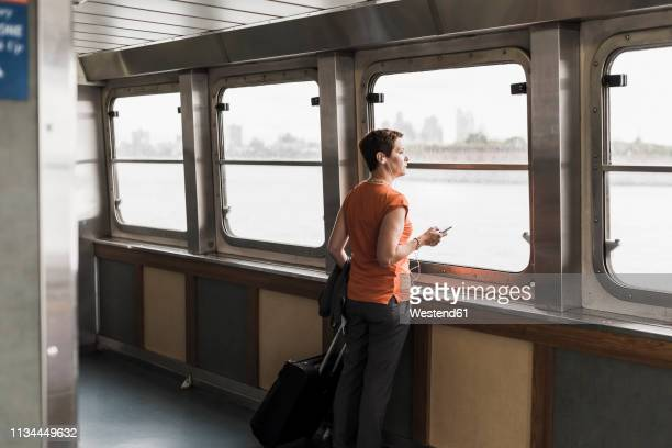 woman on a ferry looking out of window - fähre stock-fotos und bilder