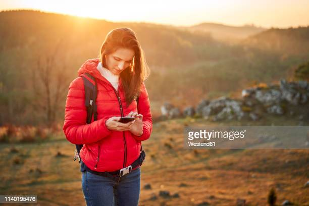 woman on a hiking trip in the mountains using cell phone - red jacket stock pictures, royalty-free photos & images
