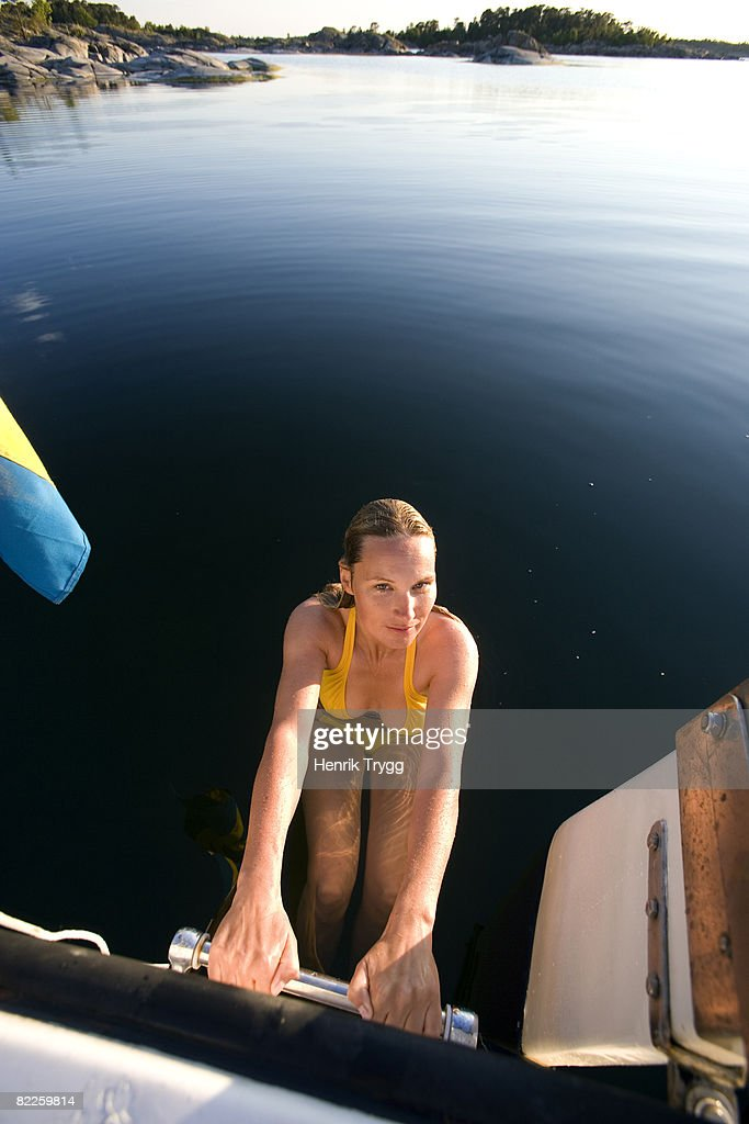 A woman on a ladder on a boat Ostergotland Sweden. : Stock Photo